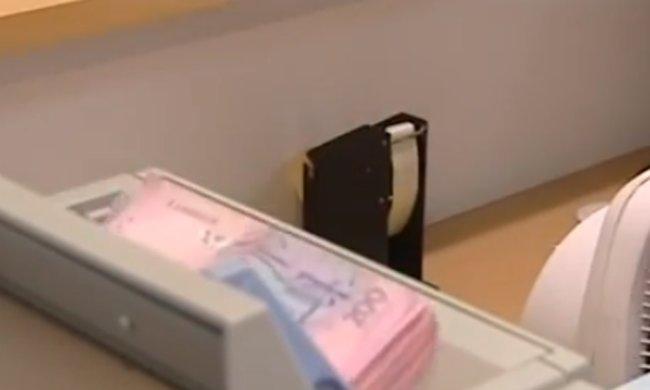 Деньги в банке, фото: Скриншот YouTube